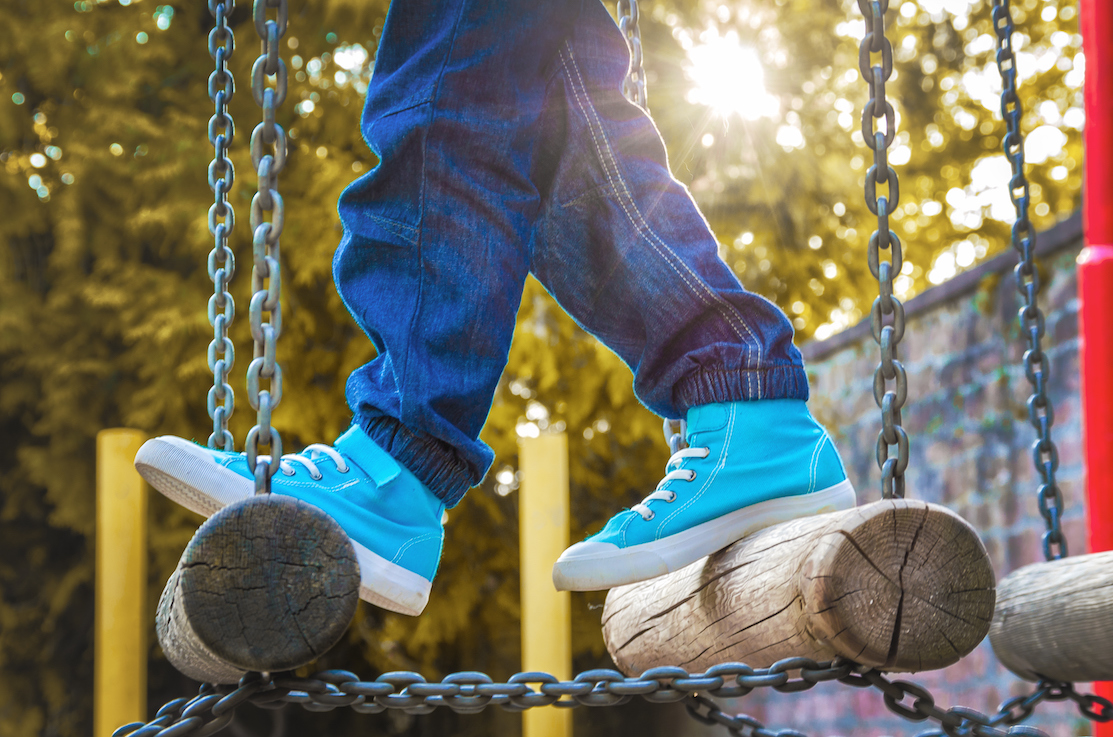 Children's feet in sneakers on the playground with obstacles